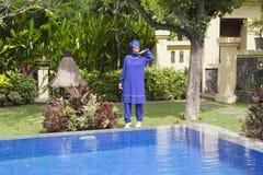 一回教游泳衣burkini的可爱的妇女在水池边在一个热带庭院里 库存照片
