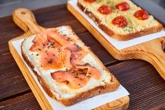 一在一个轻的切板和褐色的套三明治用熔化乳酪和各式各样的蕃茄和被烘烤的乳酪和三文鱼求爱 库存图片