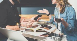 一在一见面 配合,年轻设计师坐在桌上在办公室并且采摘在编目的结束的材料 免版税库存图片