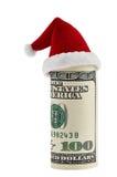 一在圣诞节圣诞老人帽子的一百美元卷 库存照片
