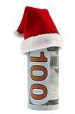 一在圣诞节圣诞老人帽子的一百美元卷 免版税图库摄影