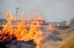 一场森林火灾和一辆消防车在城市之外 图库摄影