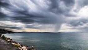 一场风暴在城市前面的海 库存照片