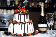 一块两层白蛋糕用新鲜水果和巧克力在一个瓶香槟和两bokalam旁边站立 免版税库存照片