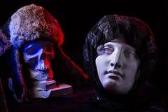 一块人为头骨和一个女性面孔雕象的一幅五颜六色的静物画 库存照片