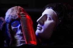 一块人为头骨和一个女性面孔雕象的一幅五颜六色的静物画 库存图片