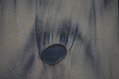 一块光滑的黑石头在沙子把它的踪影留在 免版税库存图片