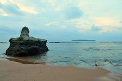 一块大石头在原始沙滩的风平浪静水域中与在早晨多云天空-西塔普尔,尼尔海岛,安达曼,印度的颜色 免版税库存图片