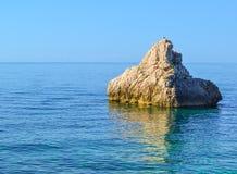 一块大石头在水上上升 亚得里亚海 夏天 没有波浪的安静的海 免版税库存图片