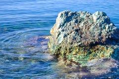一块大石头在水上上升 亚得里亚海 夏天 没有波浪的安静的海 库存图片