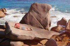 一块大石头的美丽的女性反对海在塞舌尔群岛 免版税库存图片