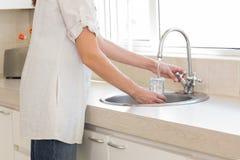 一块妇女洗涤的玻璃的中间部分在水盆的在厨房里 库存图片