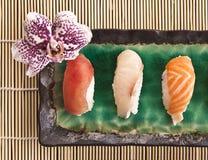 一块寿司板材的顶视图有兰花的 免版税库存照片