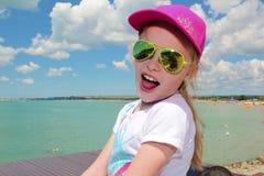 一块晴朗的黄色玻璃的愉快的小女孩 免版税库存照片
