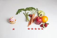 一块杯形蛋糕对 水果和蔬菜与红星报规定值 库存图片