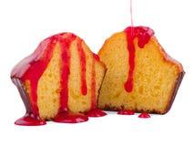 一块杯形蛋糕的两个一半用在白色背景隔绝的红色果酱 免版税库存照片