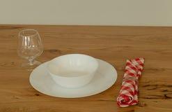 一块板材和一块玻璃在厨房木桌上 免版税库存照片