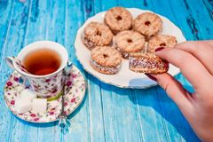 一块板材用一种油脂含量较高的酥饼和一个杯子与糖片断的红茶在蓝色木背景的 免版税库存图片