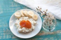 一块板材用与果子、玻璃瓶子woth春天开花和一白色鞋带亚麻布naplkin片断的酸奶干酪  免版税库存图片