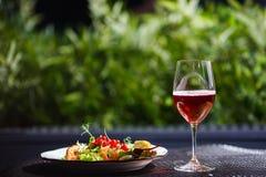 一块板材用新鲜蔬菜、虾、鹌鹑蛋和越橘美丽的开胃沙拉在与饮料的桌上 免版税库存照片