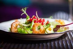 一块板材用新鲜蔬菜、虾、鹌鹑蛋和越橘美丽的开胃沙拉在与饮料的桌上 库存照片