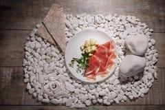 一块板材的顶视图用美丽的开胃菜 切熏火腿、绿色叶子和羊乳干酪乳酪在木背景 免版税库存图片