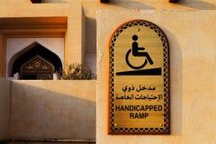 一块残疾匾用阿拉伯语和英语在对清真寺的入口 库存照片