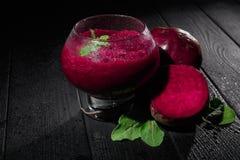 一块点心玻璃的特写镜头与深紫红色色鸡尾酒的在黑背景 健康奶昔用甜菜根,薄菏 免版税库存照片