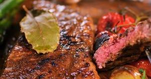 一块牛腰肉排的极端接近的视图用芦笋、土豆和烤蕃茄 免版税库存照片