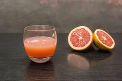 一块玻璃用新近地被紧压的葡萄柚汁 免版税库存照片