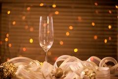 一块玻璃用香槟和金黄圣诞节球 免版税图库摄影