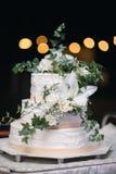 一块白色婚宴喜饼的垂直的射击与鲜花的 免版税库存照片