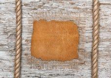 一块皮革和绳索在老木头 库存图片
