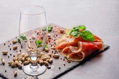 一块空的玻璃、蓬蒿叶子、开心果和红色切了在浅灰色的背景的火腿 酒客的鲜美快餐 图库摄影
