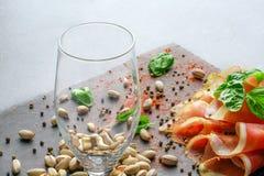 一块空的玻璃、蓬蒿叶子、开心果和红色切了在轻的盘子背景的火腿 酒客的鲜美快餐 图库摄影