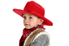一块红色牛仔帽和班丹纳花绸的逗人喜爱的年轻牛仔 免版税图库摄影