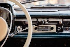 一块老汽车收音机和仪表板的减速火箭的被称呼的图象在一辆经典汽车里面 免版税库存照片