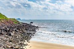 一块蓝色海天空、白色云彩和近的石头的波浪在海滩 免版税库存图片