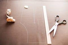 一块衣服样式模板的静物画照片与卷尺, c的 库存照片