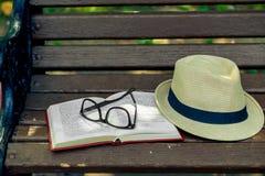 一块被忘记的新颖的书、时髦的玻璃和草帽在a说谎 库存图片