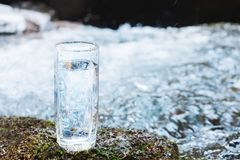 一块透明玻璃玻璃用饮用的山水在太阳beame的青苔石头站立反对a背景  库存照片