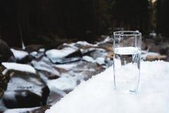 一块透明玻璃玻璃用饮用的山水在雪站立反对一条干净的山河的背景 免版税库存照片