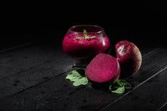 一块透明玻璃的特写镜头与深紫红色色快餐的在黑背景 健康食物用甜菜、薄菏和糖 库存图片