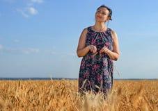 一块金黄麦田的微笑的愉快的妇女 库存图片