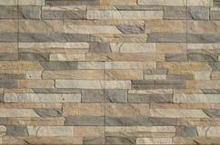 一块长的灰色和棕色砖的墙壁的细节 大厦的门面,被修造自然石头 背景textur 库存图片