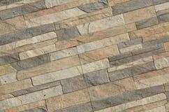 一块长的灰色和棕色砖的墙壁的细节 大厦的门面,被修造自然石头 背景textur 免版税图库摄影