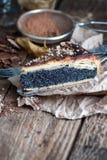 一块饼与罂粟种子的在一张老被打褶的桌上 库存图片