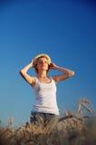 一块麦田的一个愉快的女孩 免版税图库摄影