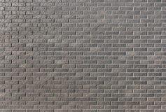 从一块黑暗的砖的墙壁与一个样式在作为a的一个明亮的晴天 免版税库存图片