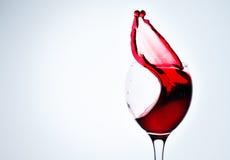 一块玻璃用红葡萄酒和浪花 免版税图库摄影